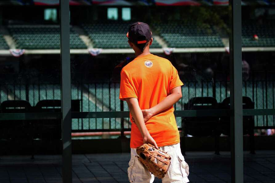 A young Houston Astros fan watches batting practice from outside the stadium while waiting for the g