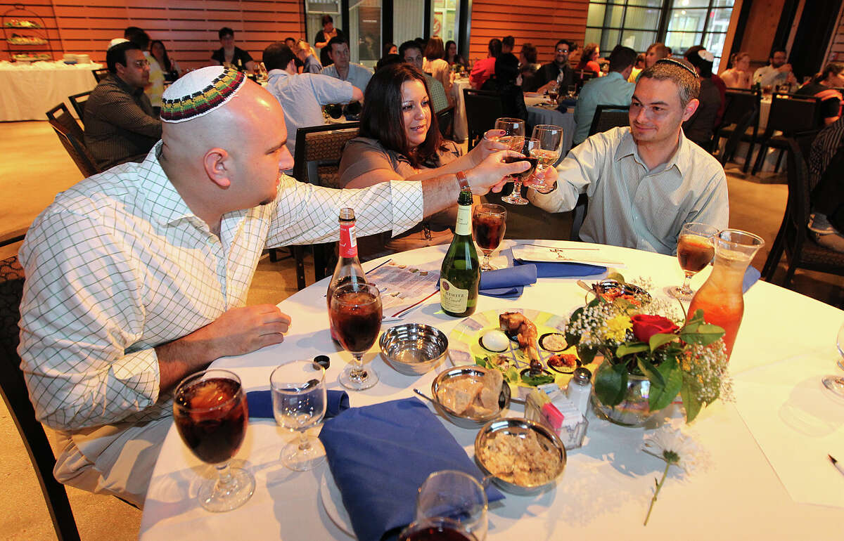 Eduardo Sonnenschein (from left), Crystal Cox and David Kisel make a toast during a Seder at The Pearl Studio.