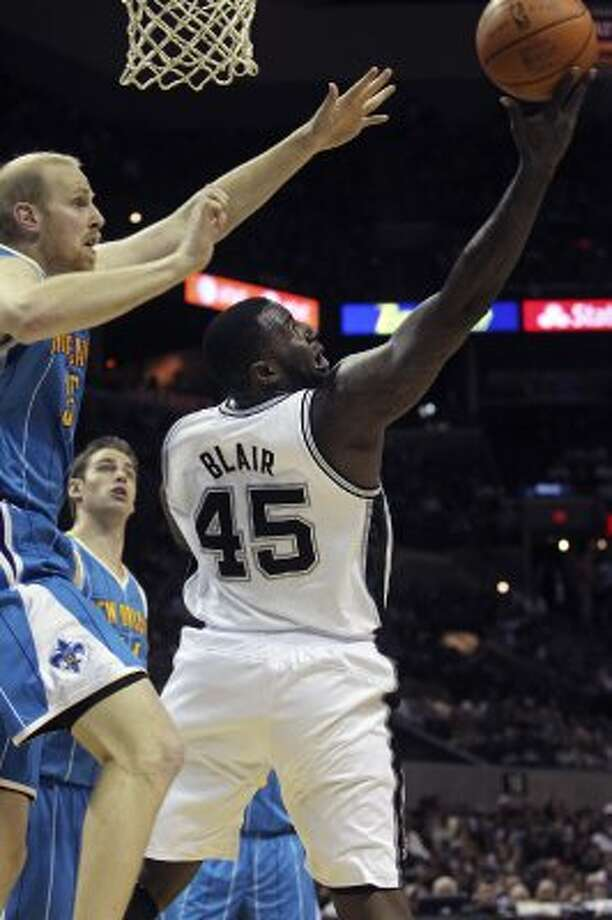 DeJuan Blair scores from the backdoor on Chris Kaman as the San Antonio Spurs play the New Orleans Hornets at the AT&T Center on April 6, 2012.  Tom Reel/ San Antonio Express-News (TOM REEL / San Antonio Express-News)
