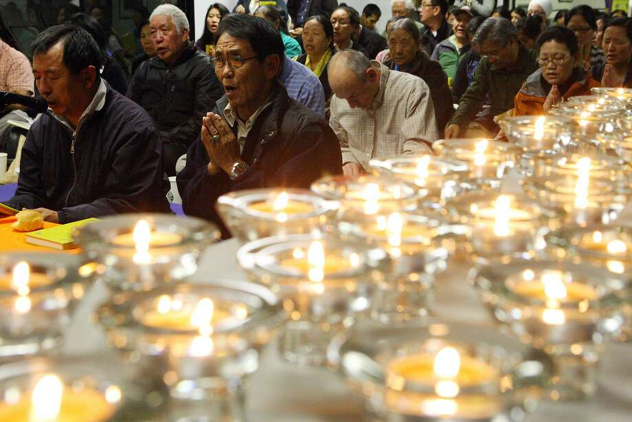 Members of the Tibetan Association of Northern California pray during a ceremony on Friday to remember the victims of the Oikos University Shooting. Photo: Erik Verduzco, The Chronicle