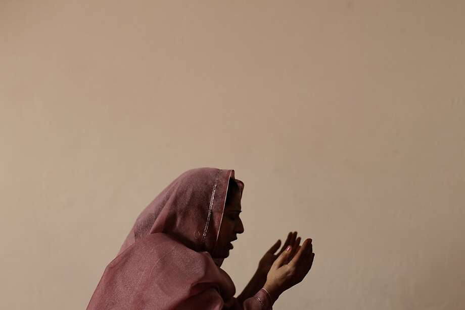 A Pakistani Christian woman prays during a Mass on Good Friday in a church in Islamabad, Pakistan, Friday, April 6, 2012. Christians around the world are marking the Easter holy week. (AP Photo/Muhammed Muheisen) Photo: Muhammed Muheisen, Associated Press