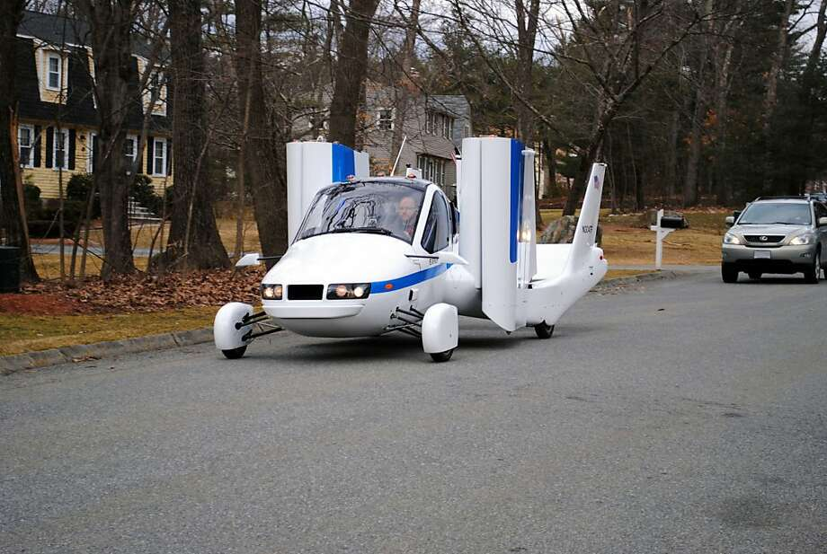 In this undated photo provided by Terrafugia Inc., the company's prototype flying car, dubbed the Transition, travels down a street with its wings folded.  The vehicle has two seats, four wheels and wings that fold up so it can be driven like a car, and flew at 1,400 feet for eight minutes during its test flight on March 23, 2012. Commercial jets fly at 35,000 feet. (AP Photo/Terrafugia.com) MANDATORY CREDIT Photo: Associated Press