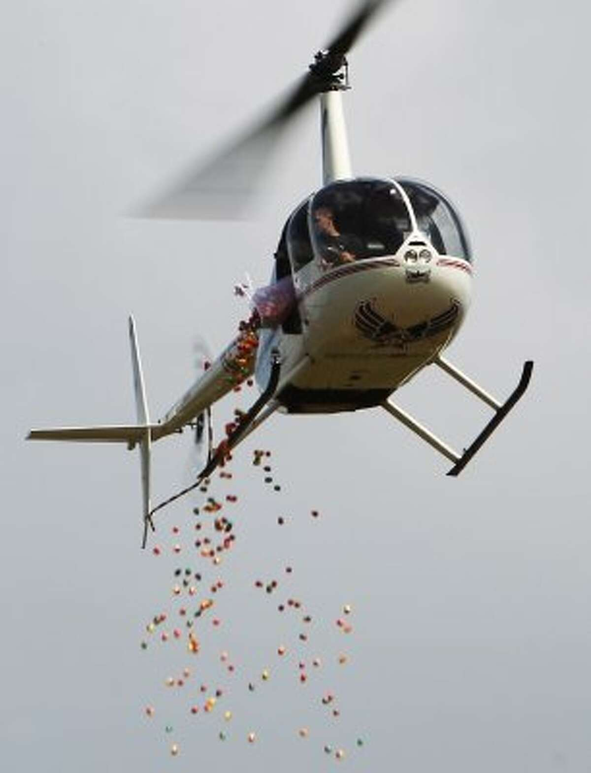 Helicopter pilot Heath Voss steadies his aircraft as plastic eggs are dropped onto a field as West U - the west campus of University United Methodist Church. (Kin Man Hui / San Antonio Express-News)