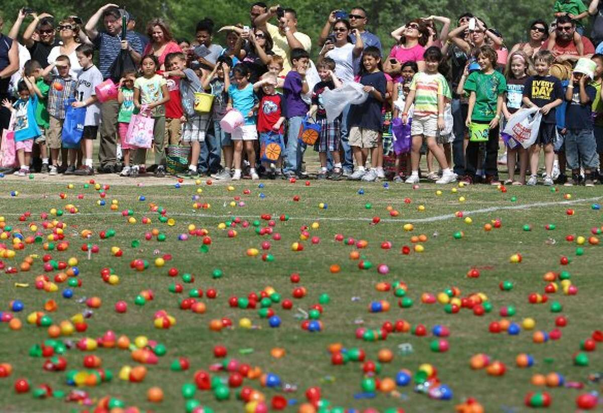Children marvel at a field full of plastic eggs awaiting to be gathered. (Kin Man Hui / San Antonio Express-News)