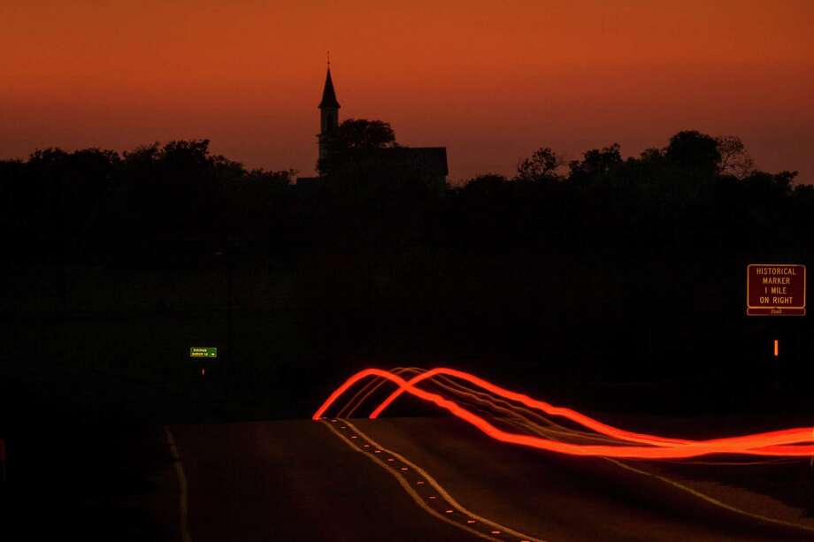 The lights from a truck traveling west on FM 2238 toward Freyburg United Methodist Church leave a trail in a time exposure photograph just after sunset. Photo: Smiley N. Pool, Houston Chronicle / © 2012  Houston Chronicle