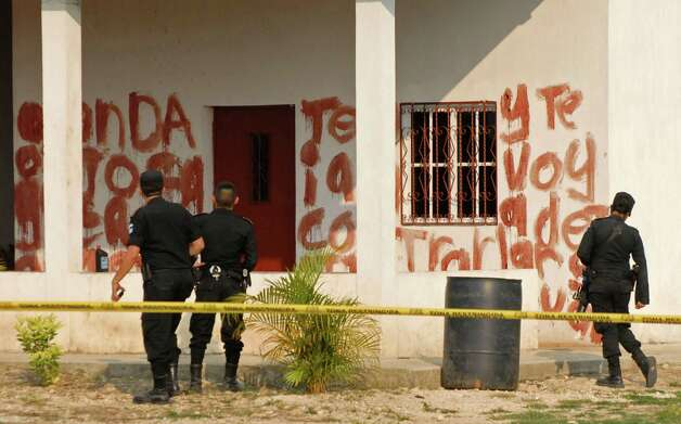 FILE - In this May 15, 2011 file photo, police agents look at a message written in blood at the site of a massacre on a ranch in the hamlet of Caserio La Bomba in La Libertad, in northern Guatemala. Authorities arrested 50 suspected members of the Zetas in connection with the massacre that left 27 people dead, 25 of those decapitated. Guatemalan authorities say they have begun to see new and disturbing evidence of an alliance between the Mara Salvatrucha street gang and the Zetas drug cartel, one of the most feared criminal organizations in Latin America, a deal with the potential to further undermine the U.S.-backed effort to fight violent crime and narcotics trafficking in the region. (AP Photo/Nuestro Diario, File) GUATEMALA OUT; NO USAR EN GUATEMALA