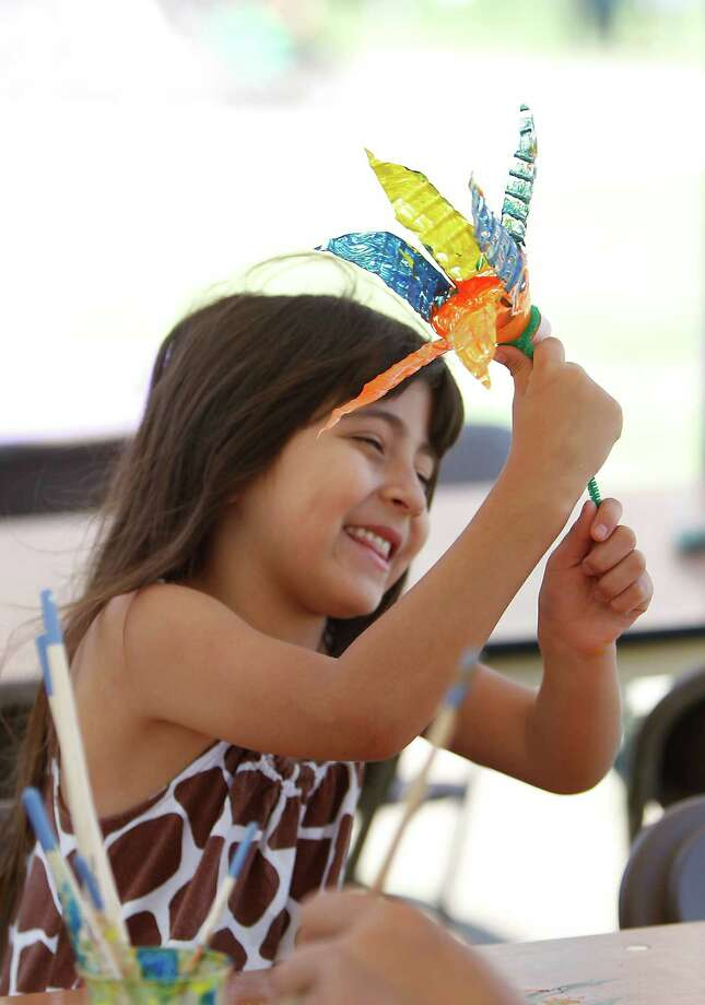 Tiffany Flores, 6, of Houston, plays with her recycled bottle flower that she made at the City Art Work's Recycle Art Zone during the Waste Management Earth Day Houston Festival at Discovery Green, Saturday, April 7, 2012, in Houston. Photo: Karen Warren, Houston Chronicle / © 2012  Houston Chronicle