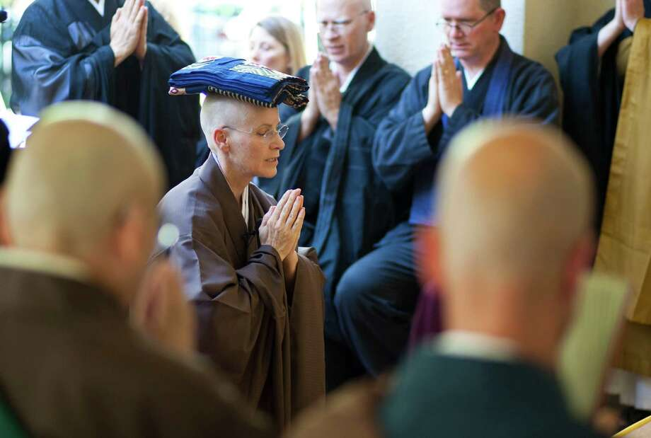 Gaelyn Godwin, center, chants as she balances her new robe on her head Saturday before ascending to the teaching seat during a ceremony marking her elevation to abbot of the Houston Zen Center. Photo: Nick De La Torre / © 2012  Houston Chronicle