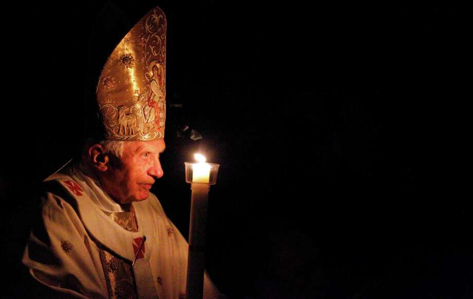 Pope Benedict XVI, holding a tall, lit, white candle, enters a hushed and darkened St. Peter's Basilica, at the Vatican Saturday, April 7, 2012, to begin the Vatican's Easter vigil service. Except for the twinkle of camera flashes, the basilica was almost pitch-black as the thousands of faithful in pews awaited Benedict's arrival through the rear entrance Saturday night. Christians on Easter joyously mark their belief that Christ rose from the dead after his crucifixion. Praying at the start of the service, Benedict said Easter brings hope to the faithful. On Sunday morning, he will lead Easter Mass in St. Peter's Square. Photo: Pier Paolo Cito, Associated Press / AP