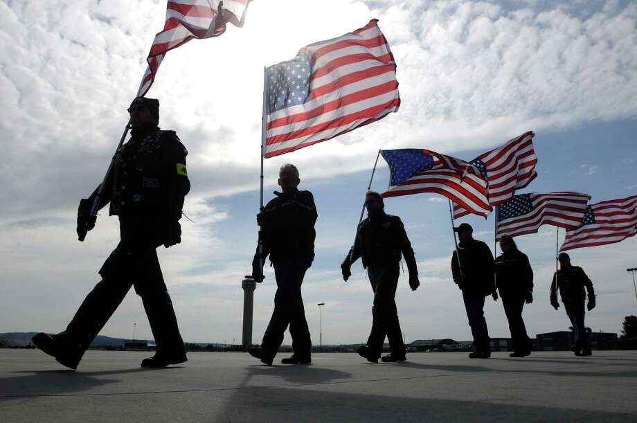 Members of the Patriot Honor Guard carry American flags across the tarmac at Gowen Field in Boise, Idaho on Saturday, April 7, 2012 following a mobilization of the Idaho National Guard for a one-year deployment to Afghanistan. Photo: Charlie Litchfield, Associated Press / Idaho Press-Tribune