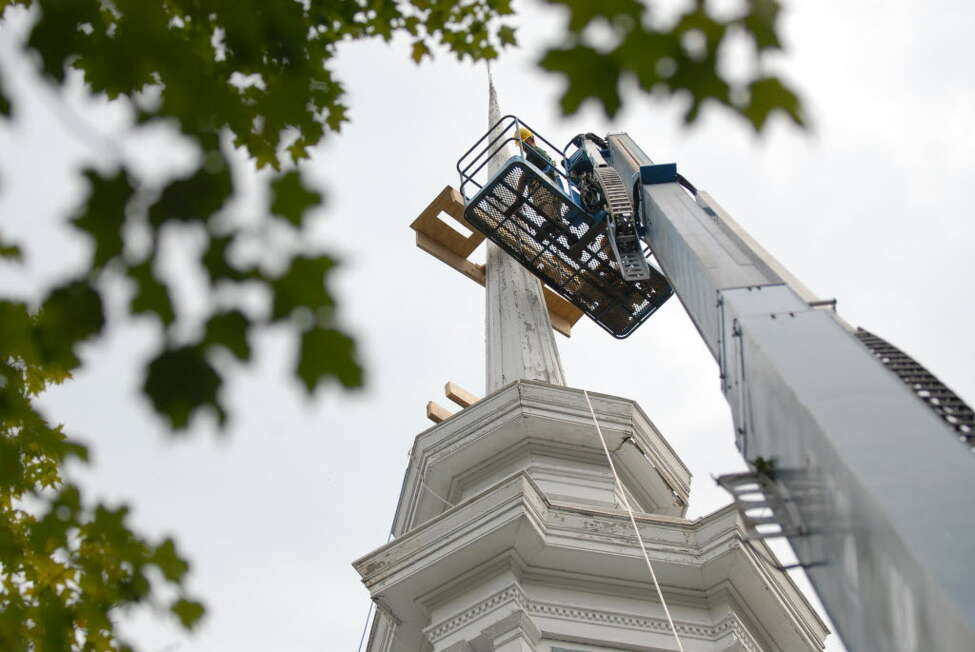 Christian Stewart of Altamont works to secure the Rensselaerville Presbyterian Church spire before removing the spire for repairs Friday morning in Rensselaerville, September 3, 2010. (Will Waldron / Times Union)
