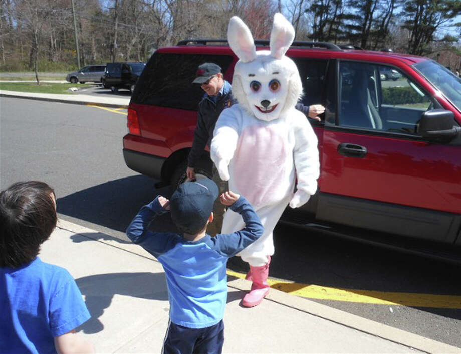 The Easter Bunny, escorted by Westport Fire Department Inspector Nate Gibbons, arrives at Long Lots School to preswide over the Greens Farms Fire Department egg hunt Saturday. Photo: Contributed Photo, Mike Lauterborn / Westport News