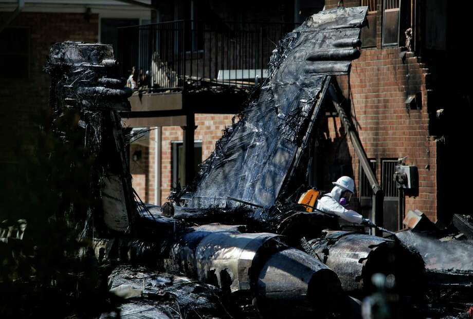 Hazardous materials workers spray down the remains of an F/A-18D Hornet jet that crashed Friday at Mayfair Mews apartments in Virginia Beach, Va., on Saturday, April 7, 2012. Photo: Preston Gannaway, Associated Press / Copyright 2012, Preston Gannaway/The Virginian-Pilot