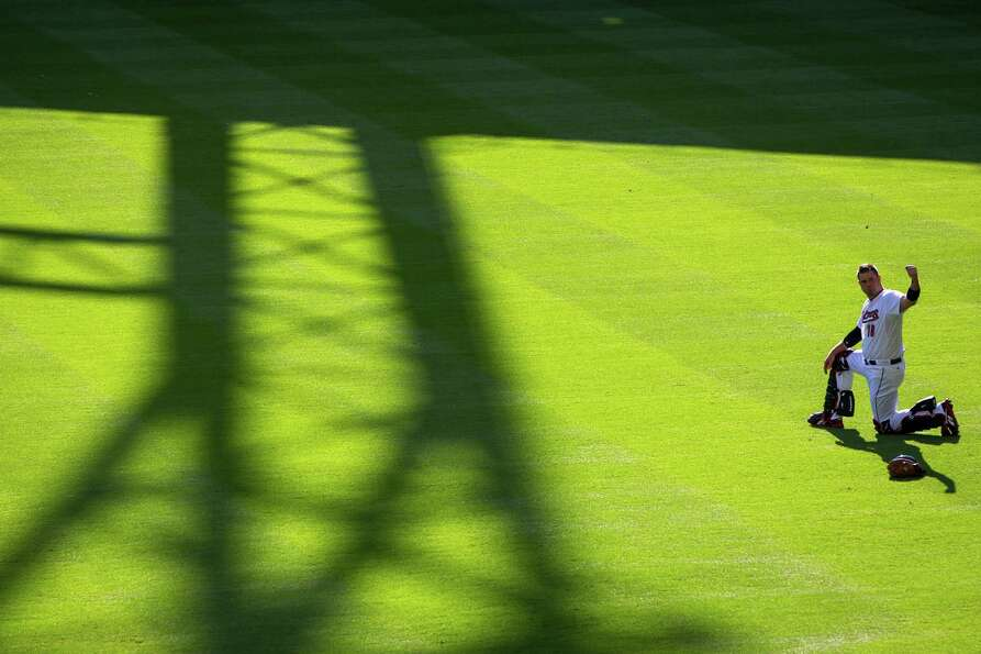 Houston Astros catcher Chris Snyder warms up in the outfield before facing the against the Colorado