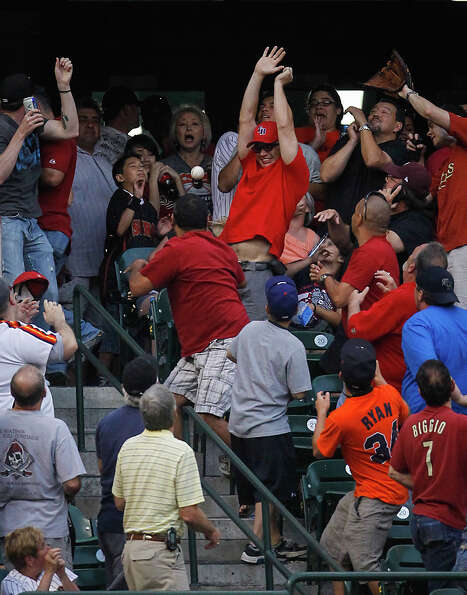 Fans in the Crawford Boxes reach for a home run ball hit by Houston Astros first baseman Carlos Lee