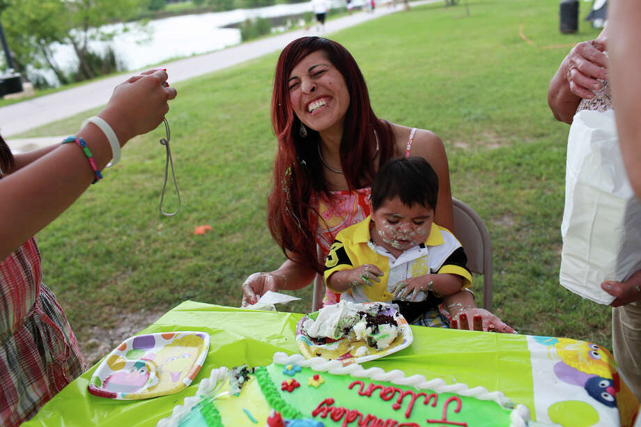"Isela Gonzalez laughs upon realizing her son, Julian Montes, 2, got himself covered with birthday cake, after his grandmother and sister put it on his face first, during his birthday party at Woodlawn Lake Park in San Antonio on Saturday, April 7, 2012. Isela Gonzalez started holding her spot on Wednesday, her first time camping at the park and participating in the tradition, to celebrate the birthday of her son, who was born premature, finding out last week that he will not be blind, despite suffering from Septo-Optic Dysplasia and Easter. ""Normally we do something small but I had to do something extra special for him,"" Gonzalez said. Lisa Krantz/San Antonio Express-News Photo: Lisa Krantz, SAN ANTONIO EXPRESS-NEWS / SAN ANTONIO EXPRESS-NEWS"