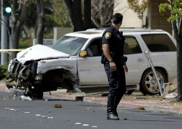 A Concord police officer turns to look at the wrecked SUV as the investigation of the scene continues after a 17-year-old male driver is being charged with manslaughter when the vehicle he was driving hit 3 bicyclists on Treat Blvd. at Oak Grove in Concord, Ca. killing a father, Soliaman Nuri, and his 9-year-old daughter Hodees Nuri, and leaving a second daughter, a 12-year-old with minor injuries, on Saturday April 7, 2012. Photo: Michael Macor, The Chronicle