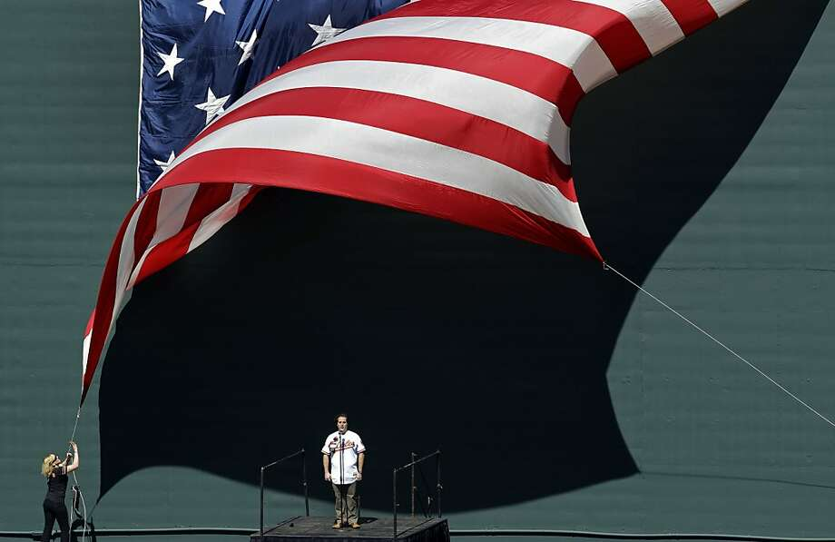 Rolando Sanz, bottom center, performs the national anthem behind the center field wall as a woman tries to pull a United States flag into place before the Baltimore Orioles' home opener baseball game against the Minnesota Twins in Baltimore, Friday, April 6, 2012. (AP Photo/Patrick Semansky) Photo: Patrick Semansky, Associated Press