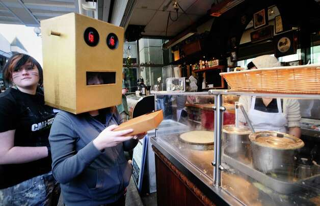 Ali McKinnon, dressed as a Shufflebot, grabs some food. Photo: LINDSEY WASSON / SEATTLEPI.COM