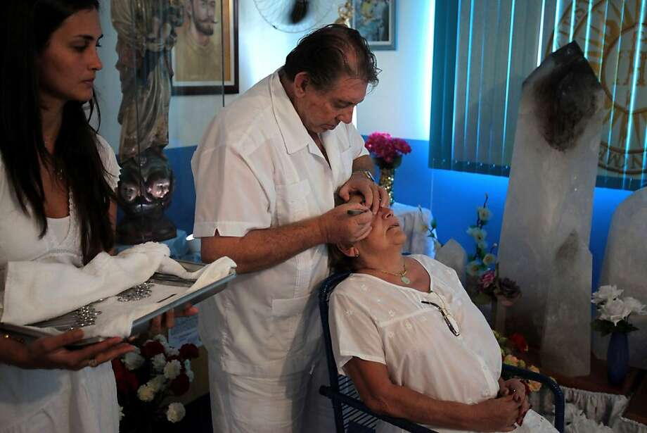 "In this Feb. 23, 2012 photo, Medium Joao Teixeira de Faria, called Joao de Deus, or""John of God,""center, uses a knife to perform a visible spiritual surgery on Jane Sousa Simoes' eyes at the ""Casa de Dom Inacio de Loyola"" in Abadiania, in the state of Goias, Brazil. The ""Casa de Dom Inacio de Loyola,"" or ""The House of Saint Inacio de Loyola,"" was founded by popular faith healer Joao Teixeira de Faria in Abadiania, Brazil in 1978, where people seek cures for illnesses. (AP Photo/Eraldo Peres) Photo: Eraldo Peres, Associated Press"