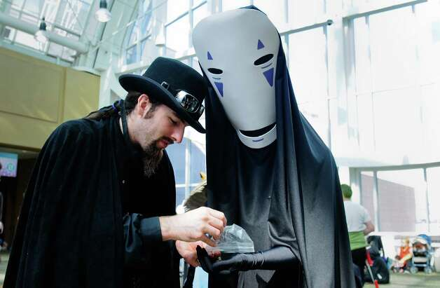 "Jake Charlton, left, gives Diedra Penner, dressed as No Face from Spirited Away, more ""offerings"" at the 15th annual Sakura-Con. Photo: LINDSEY WASSON / SEATTLEPI.COM"