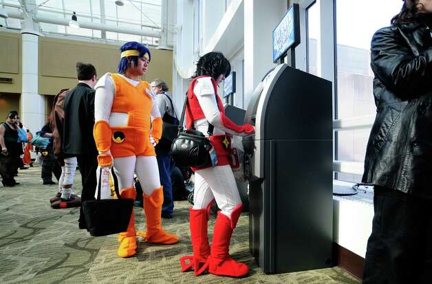 Amanda Wilson, dressed as Ryo Sanada from Ronin Warriors, right, takes money from an ATM as Krystal Refuerzo, left, waits. Photo: LINDSEY WASSON / SEATTLEPI.COM