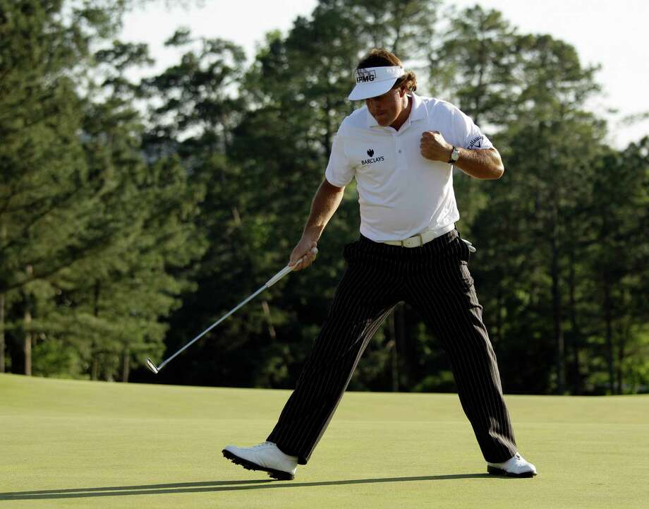 Phil Mickelson pumps his fist after a birdie putt on the 18th green during the third round of the Masters golf tournament Saturday, April 7, 2012, in Augusta, Ga. Photo: Charlie Riedel