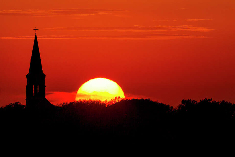 The sun sets behind St. Mary's Church in High Hill, Texas. Photo: Smiley N. Pool, Houston Chronicle / © 2012  Houston Chronicle