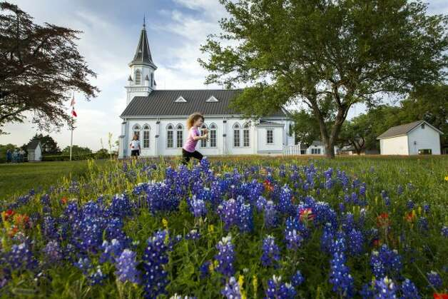 Katharina Marie Chaloupka, 4, and Mindy Girard, 9, play among bluebonnets outside Sts. Cyril and Methodius Church in Dubina. (Smiley N. Pool / Houston Chronicle)