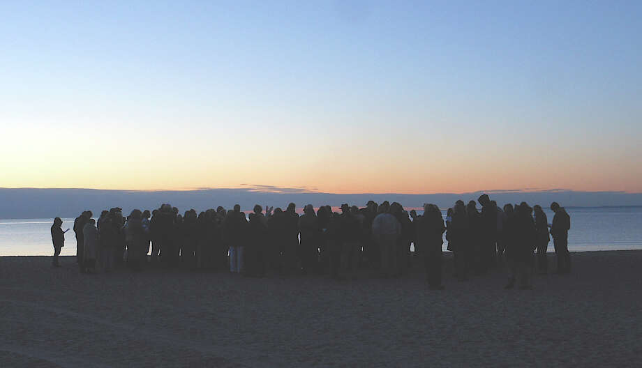 As morning dawned, worshipers gathered Sunday at Compo Beach for the annual sunrise Easter service. Photo: Contributed Photo, Mike Lauterborn / Westport News