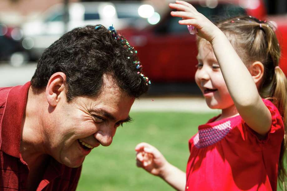 Victor Delarosa (left) has a confetti egg crushed on his head by his daughter, Mariana, 6, after the Easter egg hunt at Easter at the Park presented by St. Luke's United Methodist Church, at Discovery Green, Sunday, April 8, 2012, in Houston.   The worship celebration featured a fusion of contemporary Christian and hip hop music with Faith Ayers and the Encounter Band, DJ Psycho, and the Youth Advocates Break Dancers.  The celebration continued with open circle break dancing and fun children's crafts and activities including, of course, an Easter egg hunt. Photo: Michael Paulsen, Houston Chronicle / © 2012 Houston Chronicle