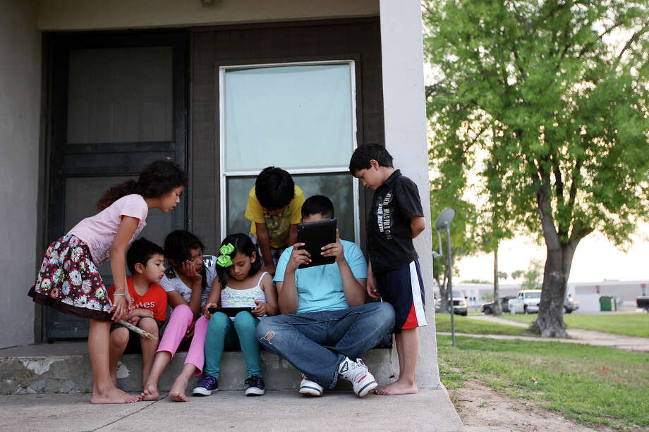 Friends and family surround Crystal Zivec, 8, center left, and Eric Garcia, 12, as they play games on iPads at the Memorial Apartments in McAllen, Tuesday, April 3, 2012. The McAllen Independent School District began handing out iPads and iPod Touch to over six thousand of the students in February. They plan on handing out the devices to the entire student population of 27,000 over the next 12 months. The Memorial Apartments is low-income housing where internet access is sparse. Students who live in the apartments rely on the few who do have access in their units or hang out by Memorial High School located across the street. They can also access the net a free wi-fi spots throughout the city. Photo: Jerry Lara, San Antonio Express-News / © San Antonio Express-News