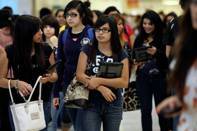 Isabel Noyola, 14, left, and Ived Sepulveda, 15, (cq), walk with their iPads at the Memorial High School campus in McAllen, Tuesday, April 3, 2012. The district began handing out iPads and iPod Touch to over six thousand of the students in February. They plan on handing out the devices to the entire student population of 27,000 over the next 12 months. Photo: Jerry Lara, San Antonio Express-News / © San Antonio Express-News