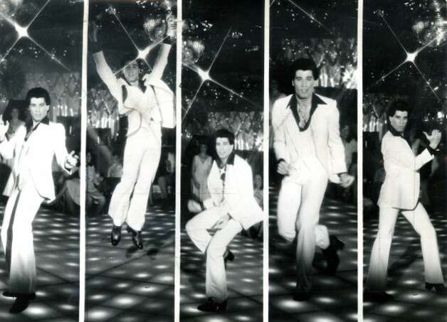 "Thanks to ""Saturday Night Fever,"" a young John Travolta wearing an open-collar, white polyester suit is etched forever in our minds. (Chronicle Archive)"