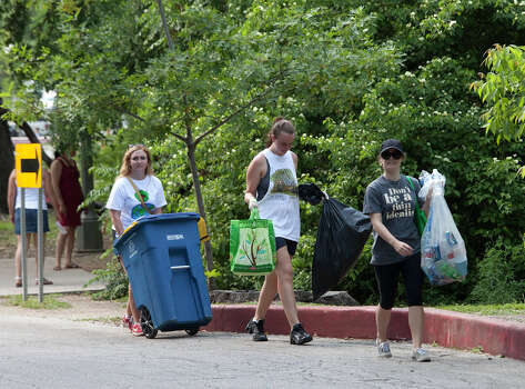 Brackenridge Park Conservancy volunteers (from the left) Mary Kaufman, Ellee Cook and Devon Rood come back from their rounds of handing out recycling bags Easter Sunday, April 8, 2012. Photo: J. Michael Short , FOR THE EXPRESS-NEWS / THE SAN ANTONIO EXPRESS-NEWS
