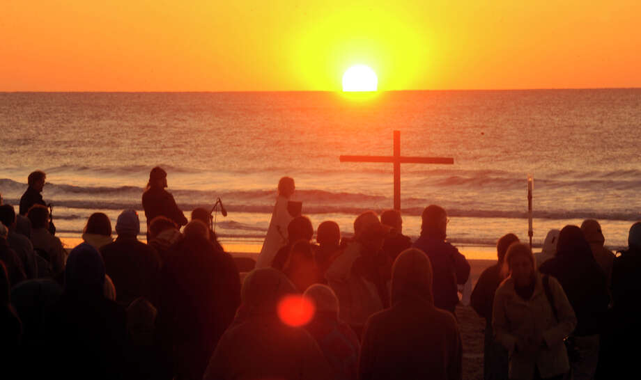 The Rev. Catherine Powell leads an early Easter service on the Wrightsville Beach dunes as the sun rises, Sunday, April 8, 2012, in Wilmington, N.C.  Wilmington's Episcopal Church of the Servant held their Easter Vigil Service on the beach. Photo: Jeff Janowski, Associated Press / Wilmington Star-News