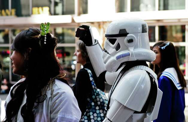 A stormtrooper takes photos of other costumed attendees. Photo: LINDSEY WASSON / SEATTLEPI.COM