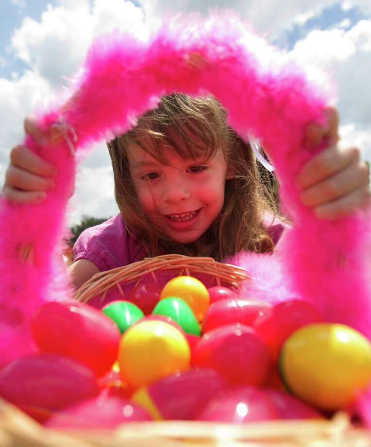 Gabriella Reynolds, 4, checks out her batch of Easter eggs after an egg hunt Sunday at Champion Life Centre church. Photo: Cody Duty / © 2011 Houston Chronicle