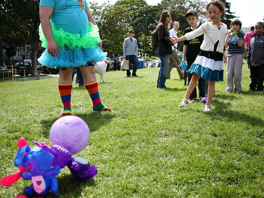 Lila Naparst, 6, tosses a ball at a row of inflatable Easter bunnies during a celebration at Dolores Park in S.F. Photo: Kevin Johnson, The Chronicle