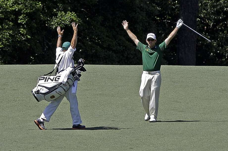 Louis Oosthuizen, of South Africa, and his caddie Wynand Stander react after Oosthuizen's double eagle two on the par 5 second hole during the fourth round of the Masters golf tournament Sunday, April 8, 2012, in Augusta, Ga. (AP Photo/Matt Slocum) Photo: Matt Slocum, Associated Press