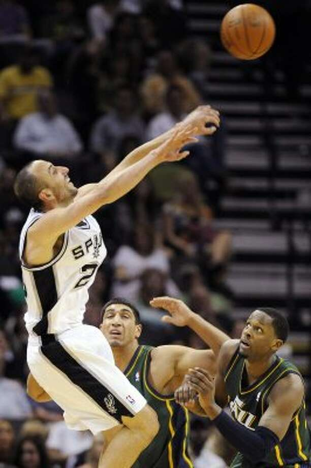 San Antonio Spurs' Manu Ginobili, left, of Argentina, shoots over Utah Jazz's C.J. Miles, right, and Enes Kanter during the first half of an NBA basketball game, Sunday, April 8, 2012, in San Antonio. (AP Photo/Darren Abate) (AP)