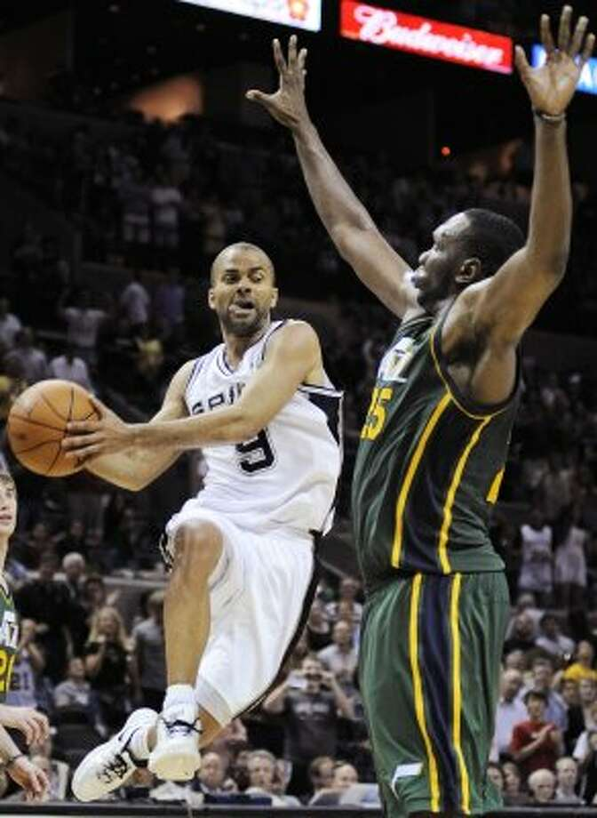 San Antonio Spurs' Tony Parker, left, of France, passes around Utah Jazz's Al Jefferson during the second half of an NBA basketball game, Sunday, April 8, 2012, in San Antonio. San Antonio won 114-104. (AP Photo/Darren Abate) (AP)