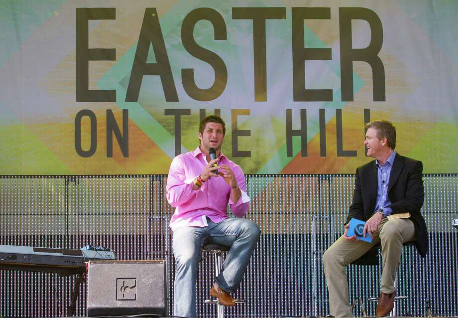 New York Jets quarterback Tim Tebow speaks with pastor Joe Champion and a crowd of 15,000 during Celebration Church's Easter service in Georgetown. Photo: William Philpott / FR170572 AP