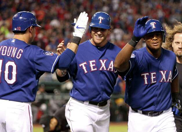 Texas Rangers' Michael Young, from left, high fives Josh Hamilton and Adrian Beltre after Beltre's homer in the fourth against the Chicago White Sox at the Rangers Ballpark in Arlington, Texas, Sunday, April 8, 2012. Photo: Richard W. Rodriguez, MCT / Fort Worth Star-Telegram