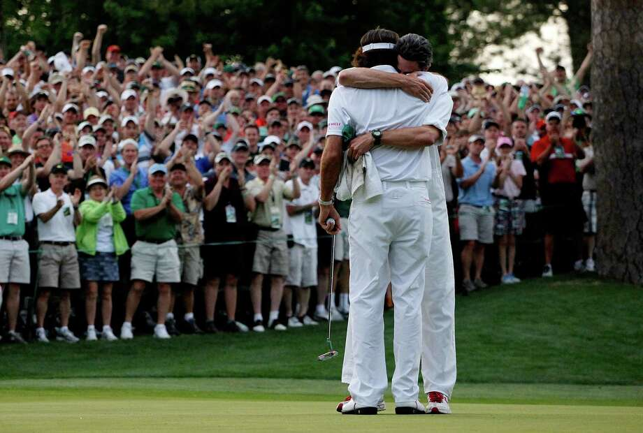 Masters champ Bubba Watson, left, hugs caddie Ted Scott after winning his sudden-death playoff on the second hole. Watson and Louis Oosthuizen tied at 10-under 278 to extend the drama. Photo: Streeter Lecka / 2012 Getty Images