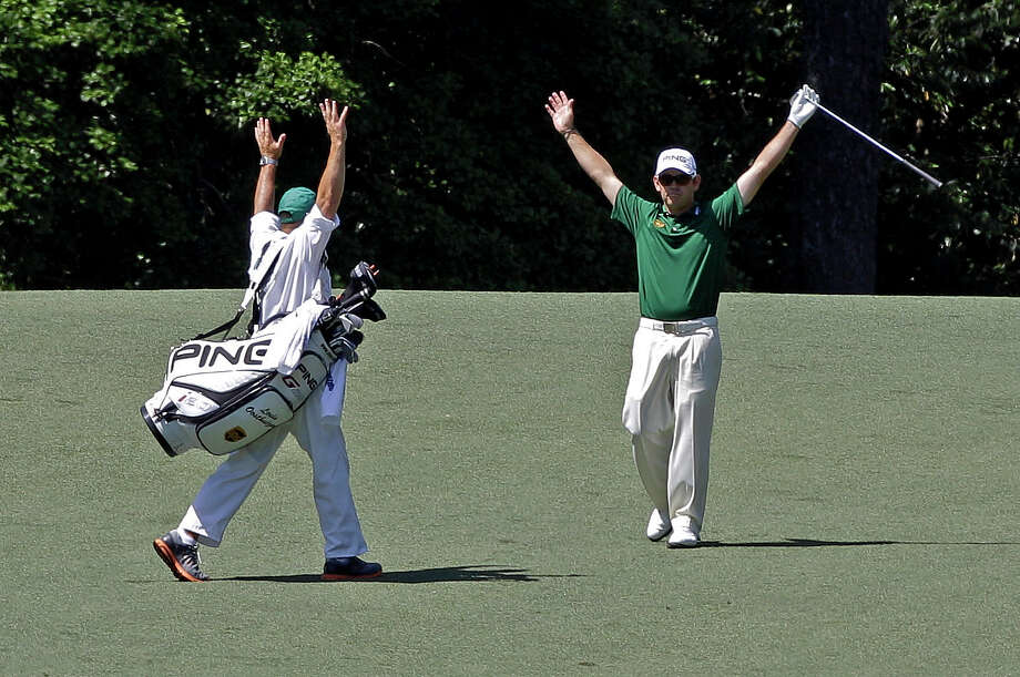 Louis Oosthuizen, right, and caddie Wynand Stander celebrate after Oosthuizen's spectacular double eagle on the par-5 second hole Sunday. Photo: Matt Slocum / AP