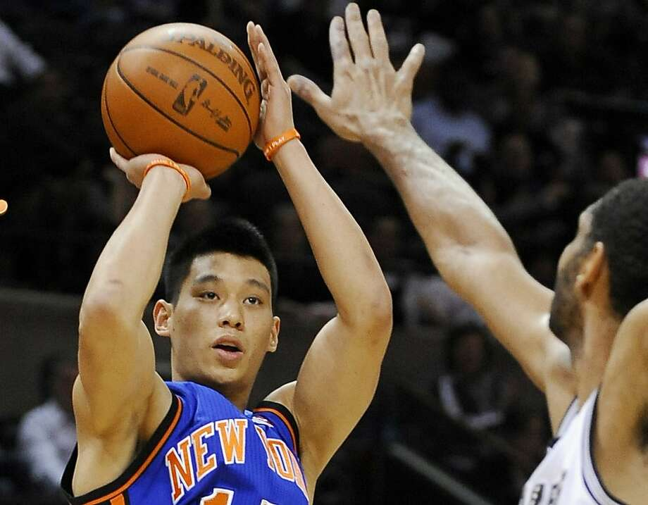 FILE - In this March 7, 2012 file photo, New York Knicks' Jeremy Lin, left, shoots over San Antonio Spurs' Tim Duncan during the first half of an NBA basketball game, in San Antonio.  Emerging NBA star Jeremy Lin has signed a two-year contract with automaker Volvo to promote the company's cars around the world but especially in Asia.  The Chinese-owned company said in statement Tuesday, March 20,  that Lin will participate in Volvo's worldwide corporate and marketing activities as a brand ambassador. The contract will focus on China, the United States and other Chinese-language markets in Asia. (AP Photo/Darren Abate, File) Photo: Darren Abate, Associated Press