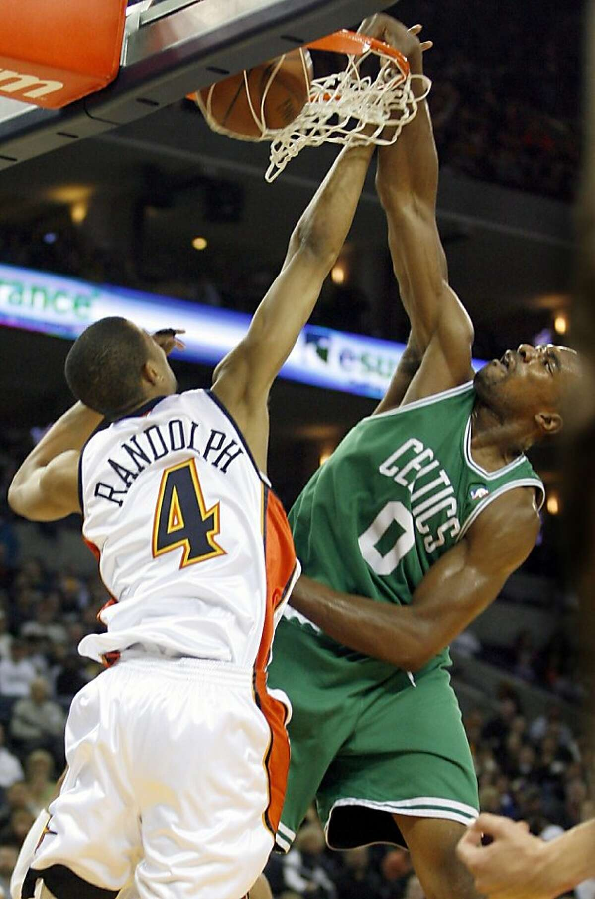 The Boston Celtics' Leon Powe dunks over the Golden State Warriors' Anthony Randolph (4) in the first half of an NBA basketball game, Dec. 26, 2008, in Oakland, Calif. (AP Photo/Dino Vournas)