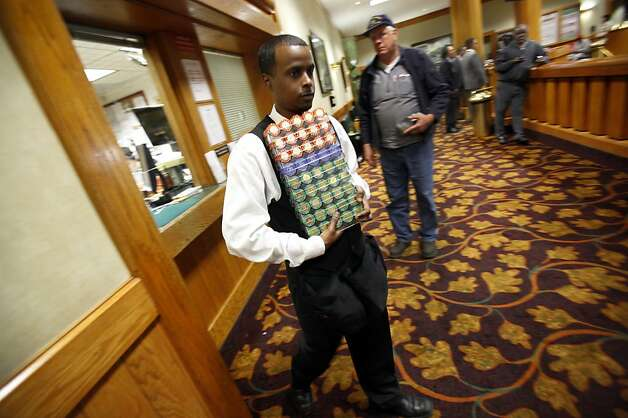 Chip runner Tecle Kidane brings poker chips to the floor at the Oaks Card Club in Emeryville, Calif., Friday, April 6, 2012.  A proposed state bill would legalize online poker and perhaps other games in the future. Card clubs like Oaks would be allowed to get a license to offer online gaming under the current draft of the legislation. Photo: Sarah Rice, Special To The Chronicle