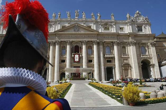 A Swiss Guard stands in front of St. Peter's Basilica as Pope Benedict XV  delivers his address prior to  the Urbi and Orbi blessing in St. Peter's Square at the the Vatican Sunday, April 8, 2012.  Pope Benedict XVI in his Easter Sunday message has urged the Syrian regime to heed international calls to end bloodshed and commit to dialogue. After celebrating Mass in St. Peter's Square, Benedict voiced hope that Easter's joy would comfort Christian communities suffering because of their faith. He denounced terrorist attacks in Nigeria that have hit Christians and Muslims alike and prayed for peace in coup-struck Mali. The pope struggled with hoarseness throughout the Mass before a crowd of more than 100,000 faithful. Only hours earlier he had led a three-hour nighttime Easter vigil inside St. Peter's Basilica. (AP Photo/Pier Paolo Cito) Photo: Pier Paolo Cito, Associated Press
